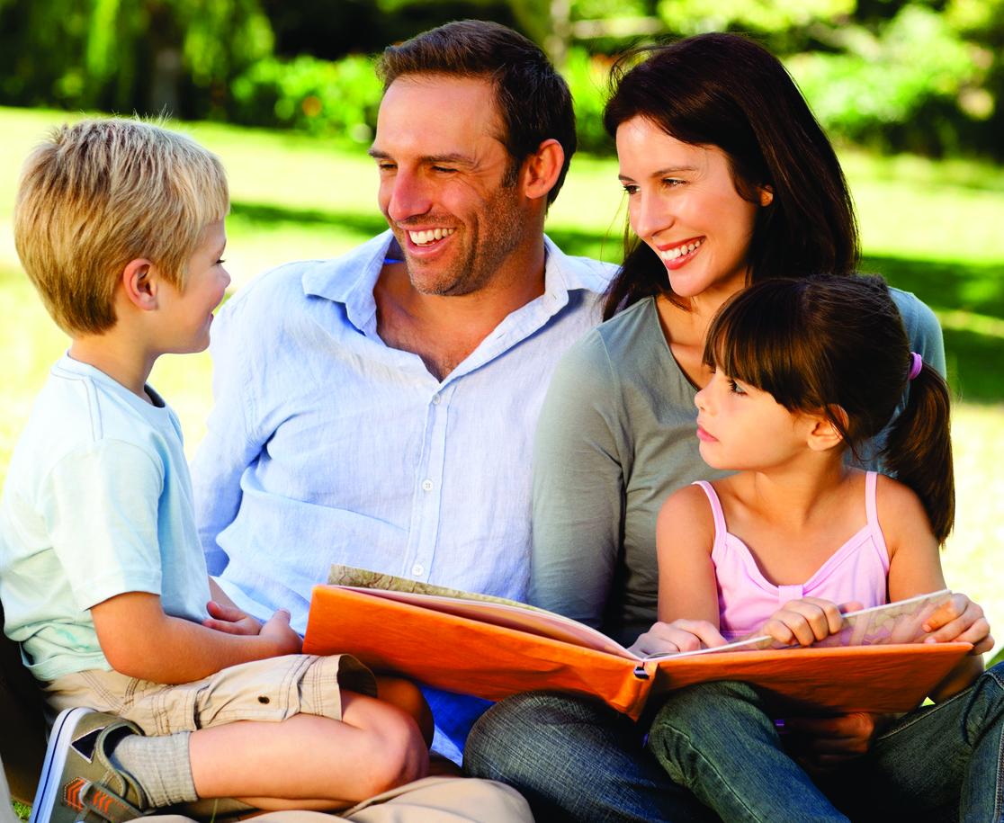 Nasmijana porodica: otac, majka, kćerka i sin sjede u parku.
