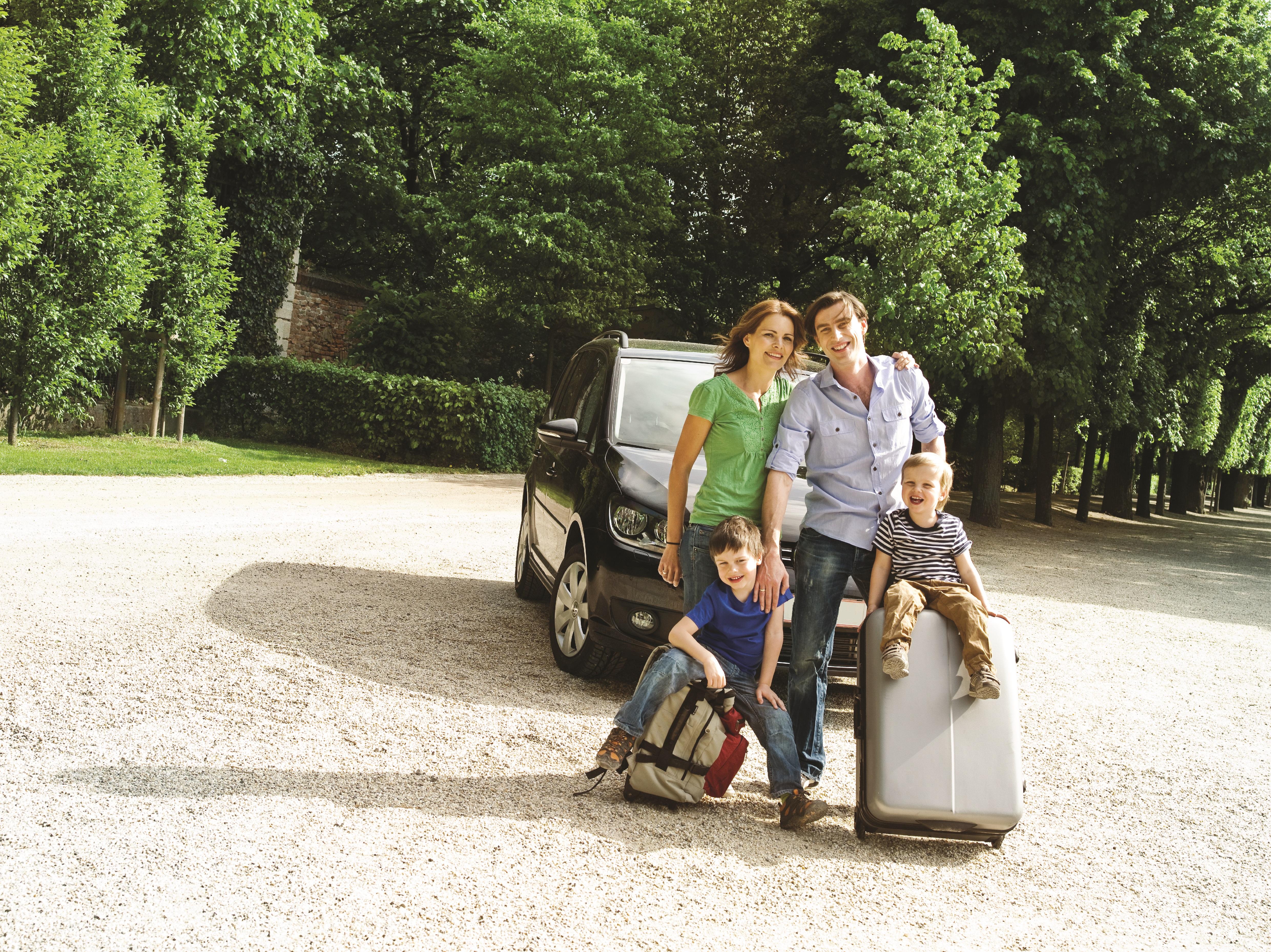 Četveročlana porodica, otac i majka u četrdesetim godinama i dvojica sinova, jedan otprilike trogodišnjak, a drugi otprilike šestogodišnjak stoje ispred parkiranog automobila. Dječaci sjede na putnim koferima i nasmijani su, roditelji se nalaze iza njih, a ispred automobila i majka je zagrila oca.
