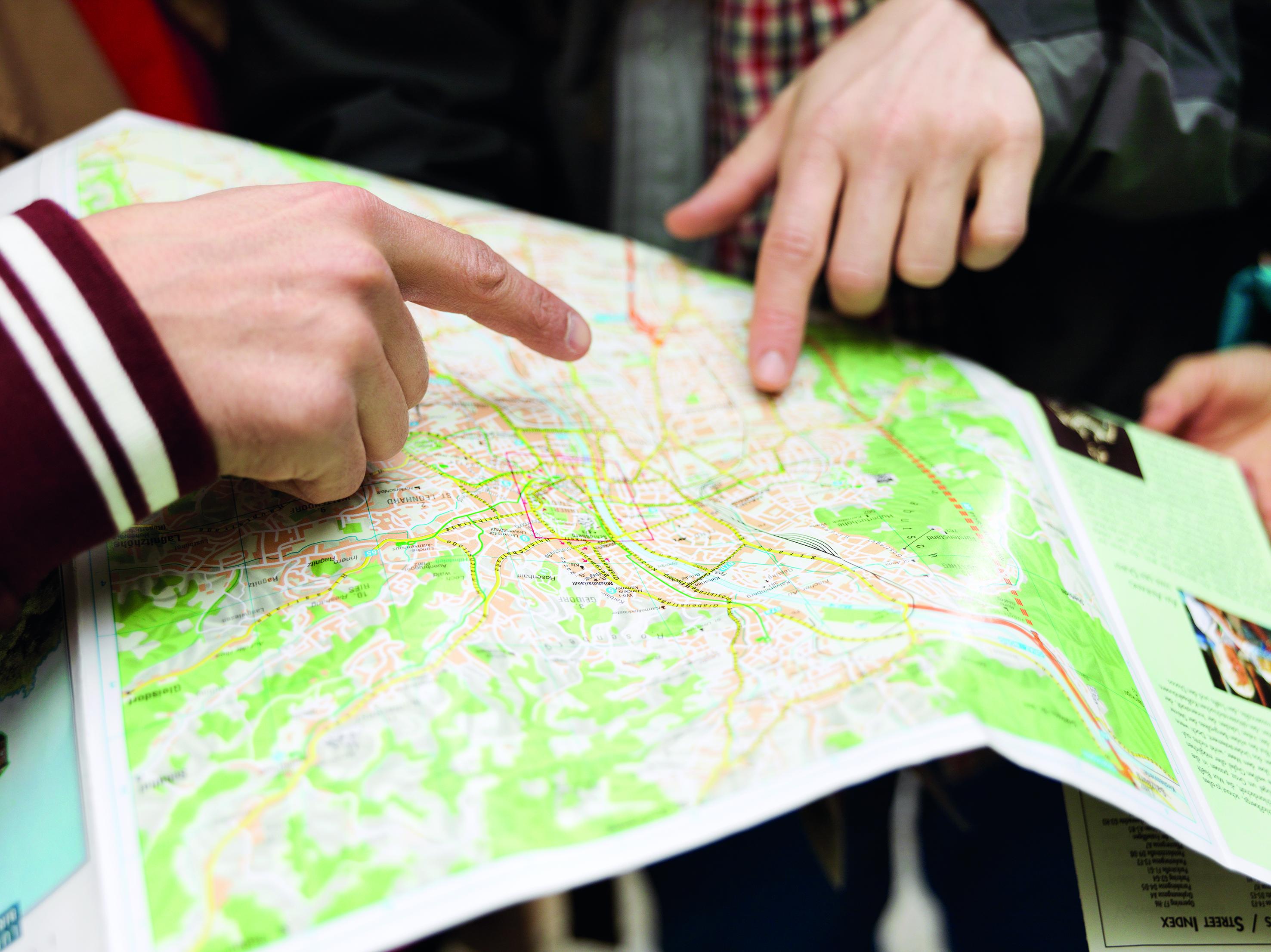 Desna i lijeva ruka dvojice muškaraca pokazuje dva mjesta na papirnoj mapi grada