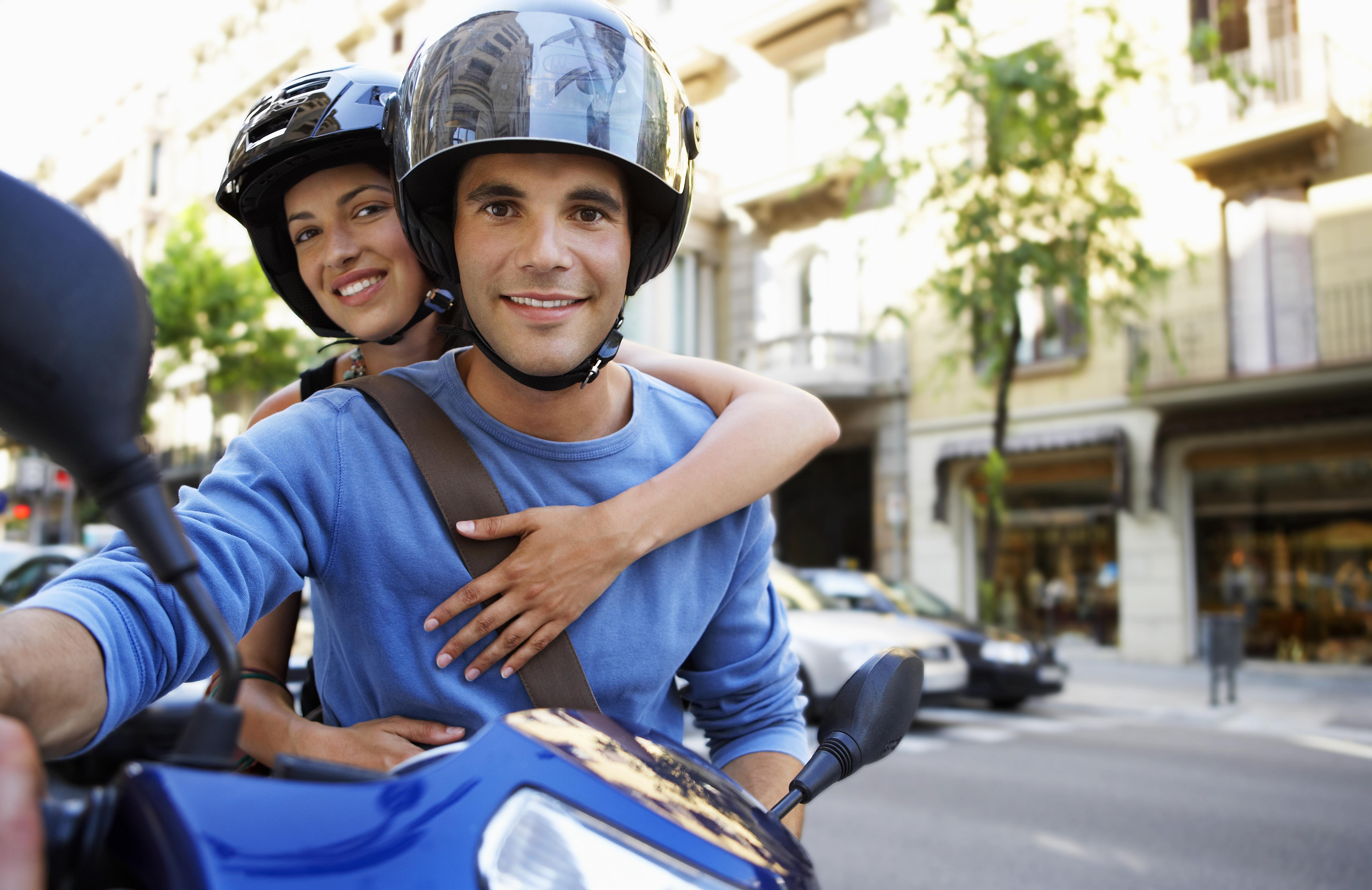 Momak u dvadesetim godinama vozi motor, a djevojka sjedi iza njega i zagrila ga je, oboje imaju kacigu na glavi.