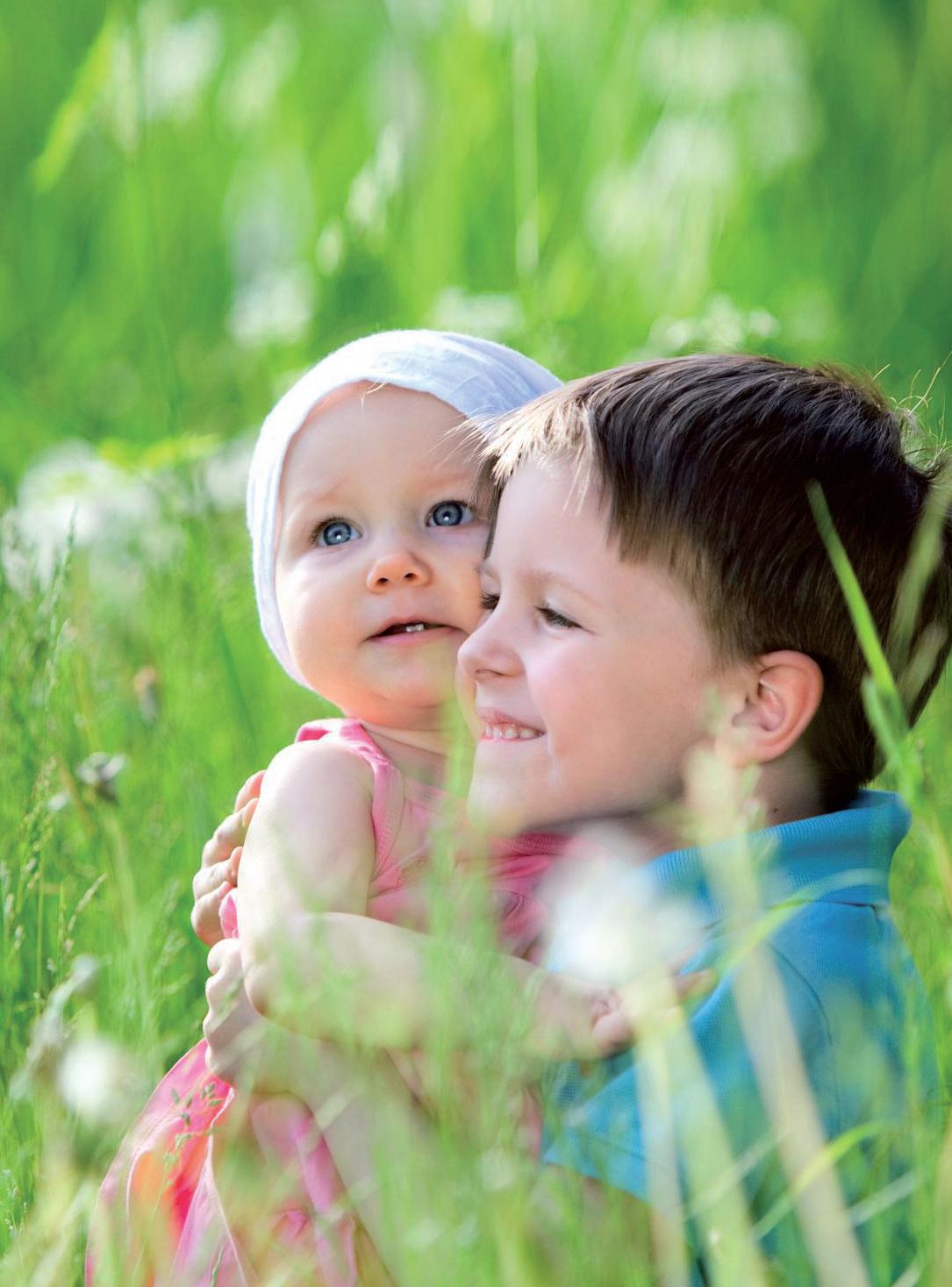 Četverogodišnji brat drži u zagrljaju sedmomjesečnu sestru na livadi.