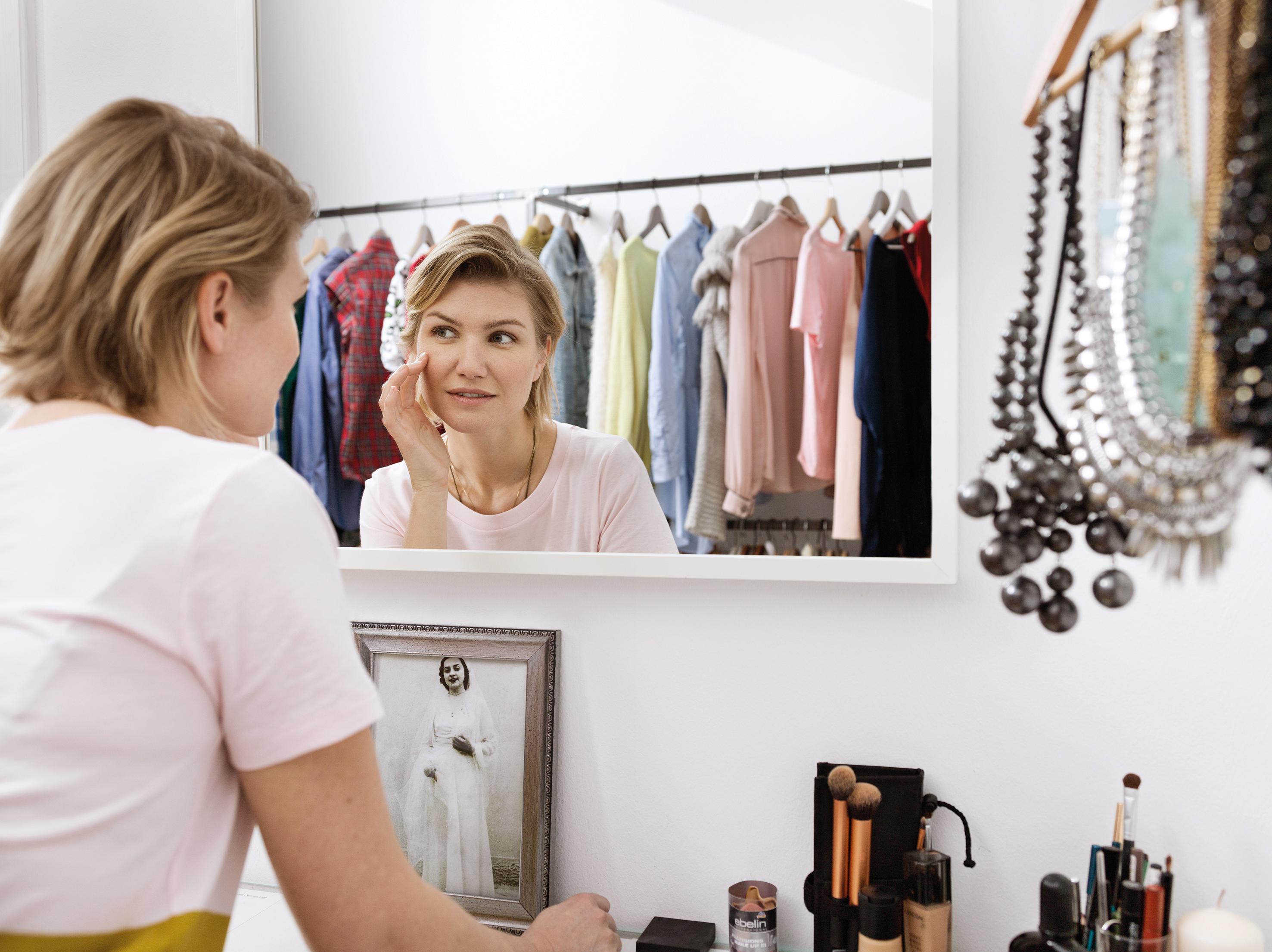 Plavokosa žena ranih srednjih godina, se ogleda u ogledalu u garderobi, i vidi se njen blagi odraz lica.