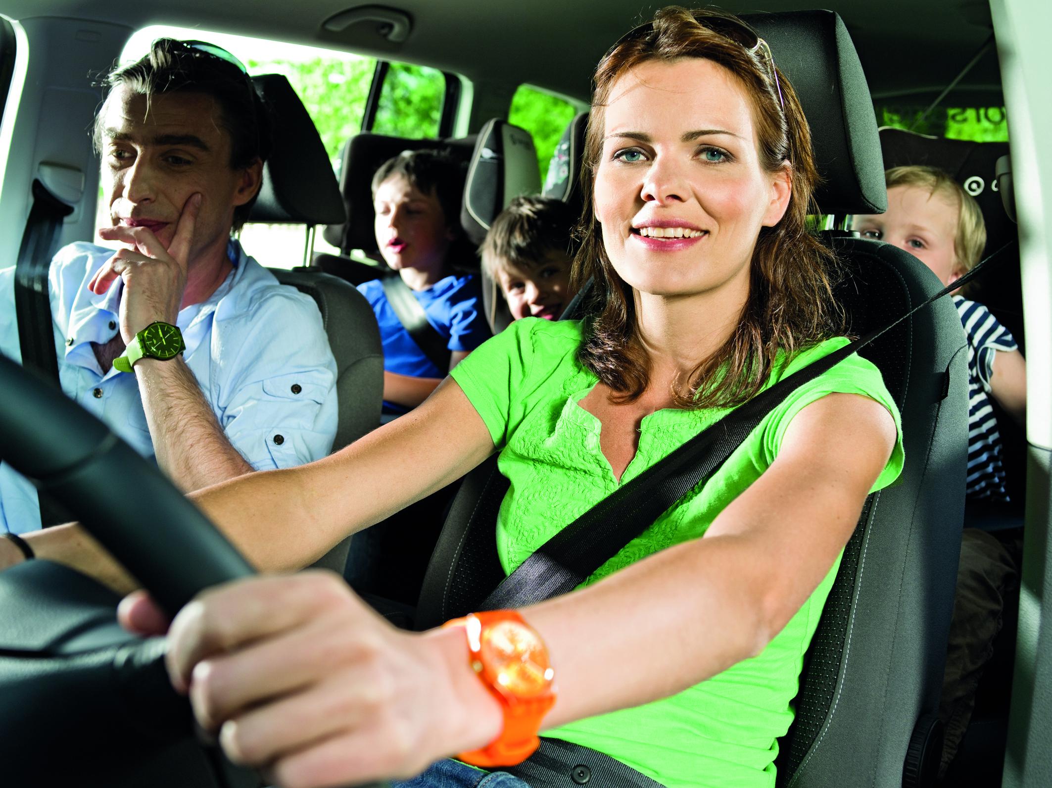 Žena sjedi u svijetlozelenoj majici na vozačevom mjestu, svezana sigurnosnim pojasem, drži volan, a iza nje izviruju dječak i djevojčica.