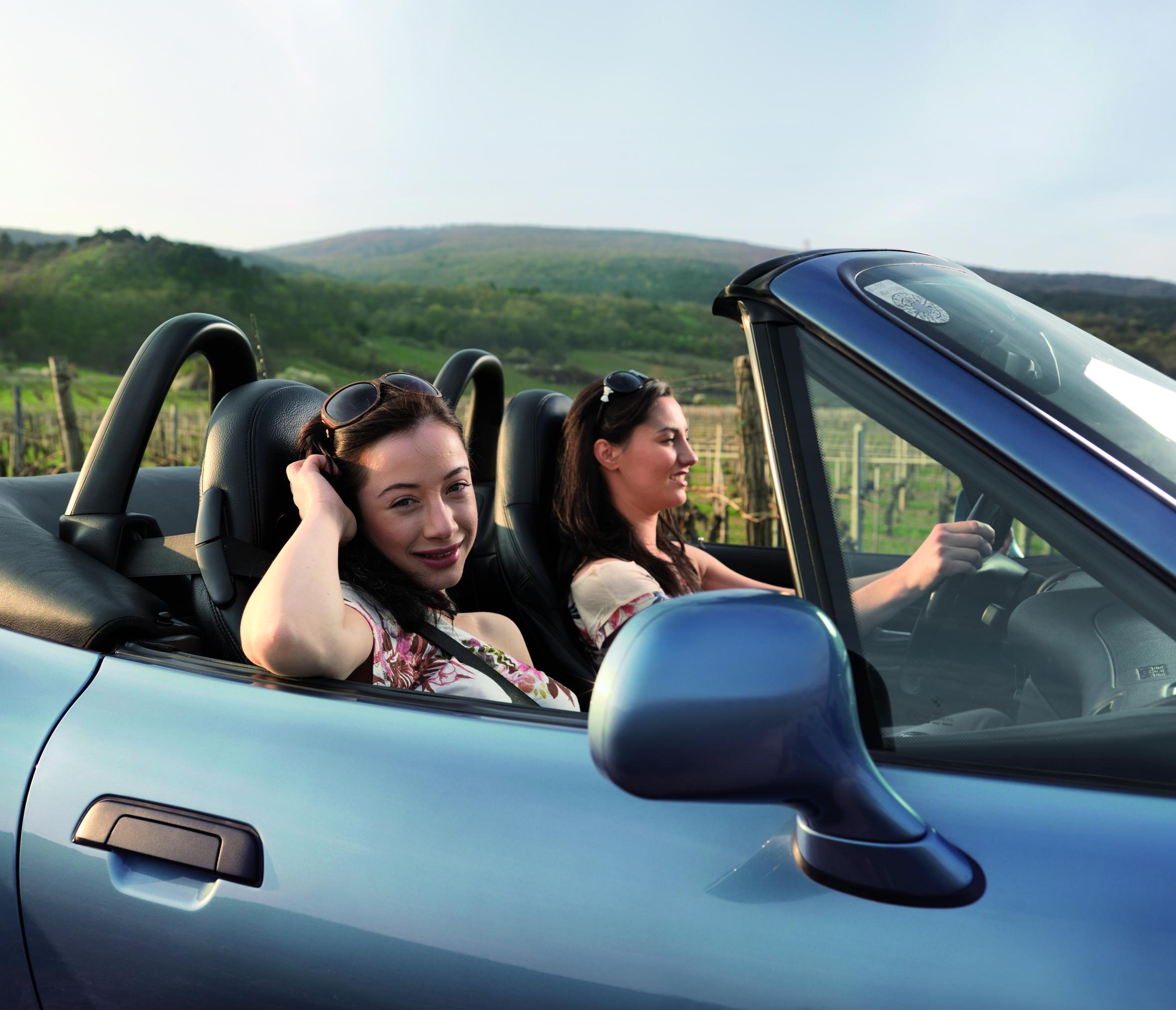 Dvije mlade djevojke u kabriolet automobilu se voze sa osmijehom, a u pozadini se vidi lijep pejzaž vinograda.