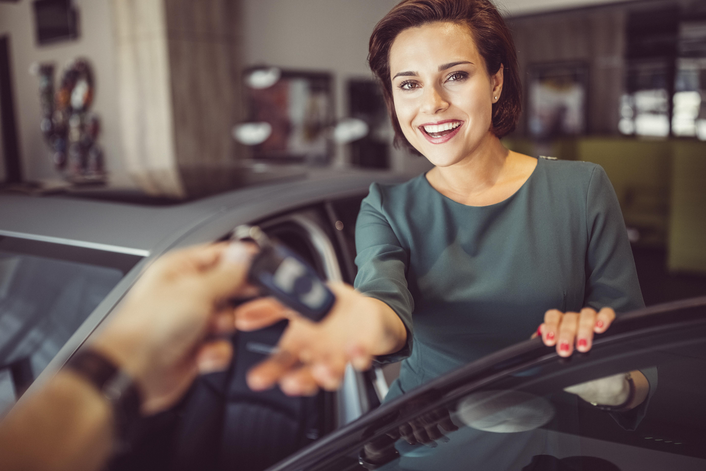 Gospođa srednjih godina tamnosmeđe kose uzima ključeve od automobila od neke ruke čije obrise naziremo.