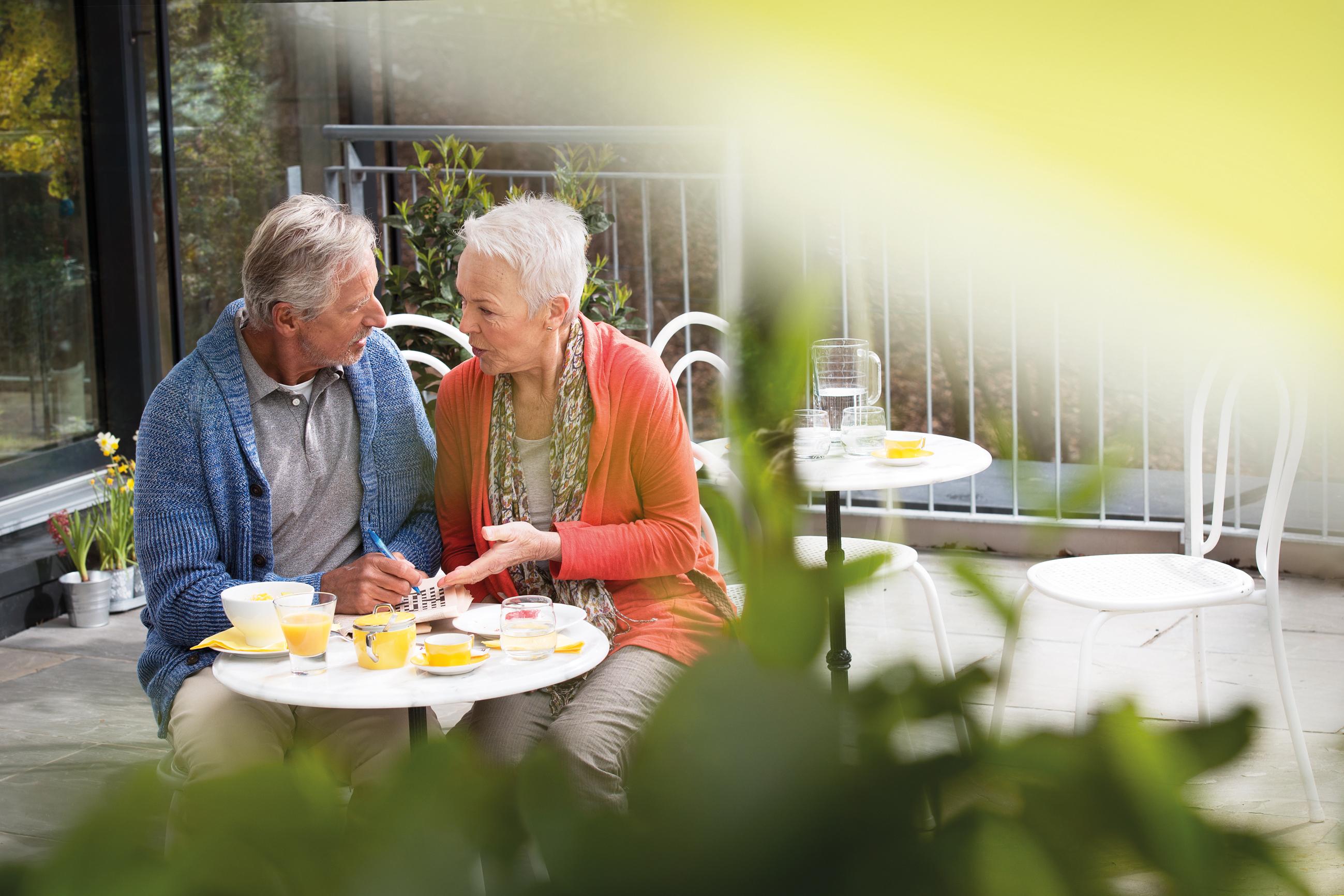 Stari bračni par razgovara za stolom u kafiću